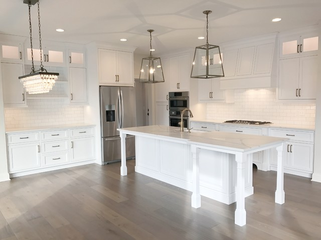 Inspiration for a large farmhouse l-shaped medium tone wood floor and brown floor kitchen remodel in Cleveland with an undermount sink, shaker cabinets, white cabinets, white backsplash, subway tile backsplash, stainless steel appliances and an island