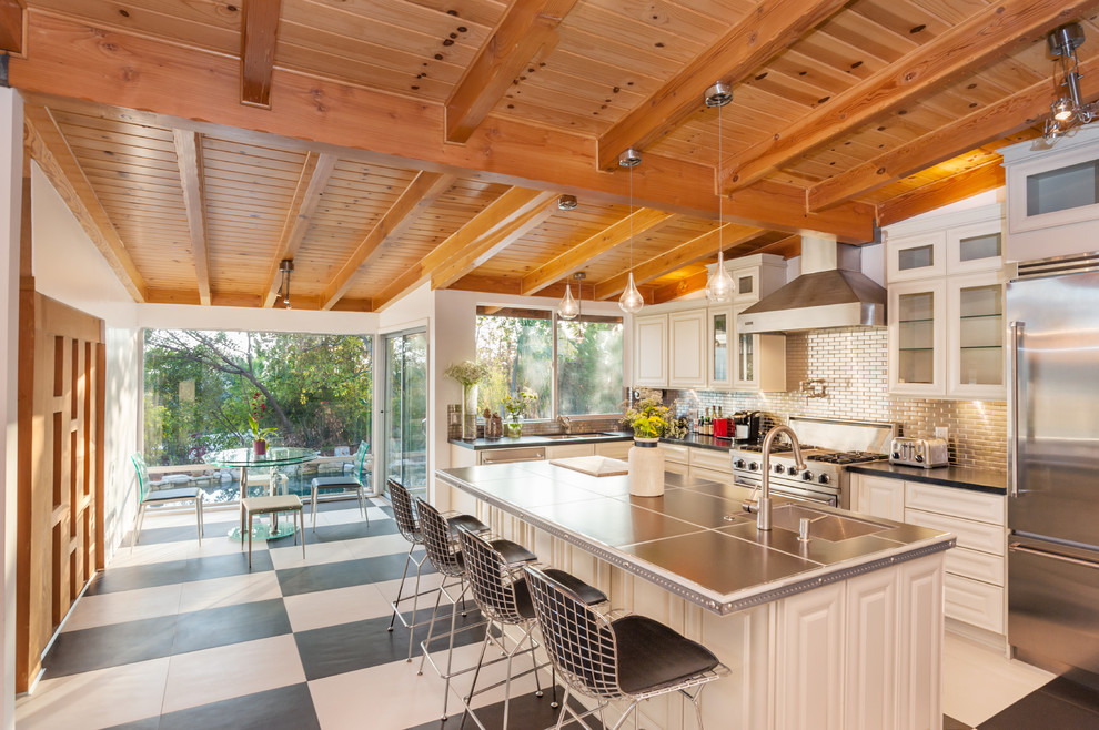 Inspiration for a large transitional l-shaped eat-in kitchen remodel in Los Angeles with an undermount sink, raised-panel cabinets, white cabinets, metallic backsplash, metal backsplash, stainless steel appliances and an island