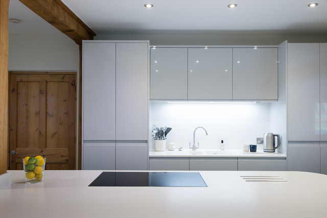Large minimalist galley slate floor and gray floor open concept kitchen photo in Cornwall with a farmhouse sink, glass-front cabinets, white backsplash, glass sheet backsplash, black appliances, an island, white countertops and gray cabinets