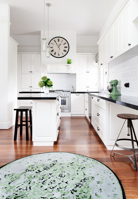 Photo of a transitional l-shaped kitchen in Melbourne with a farmhouse sink, recessed-panel cabinets, white cabinets, white splashback, subway tile splashback, stainless steel appliances, medium hardwood floors, an island and black benchtop.