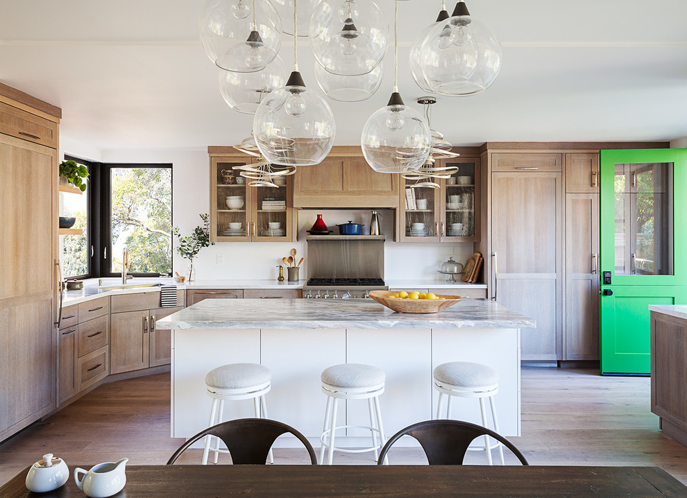 Example of a transitional l-shaped medium tone wood floor and brown floor eat-in kitchen design in San Francisco with shaker cabinets, medium tone wood cabinets, paneled appliances and an island