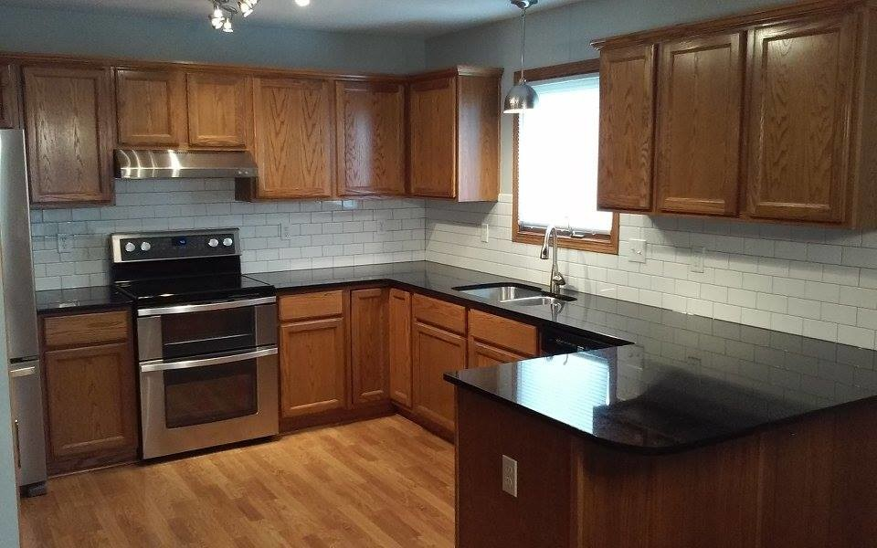 Inspiration for a mid-sized timeless l-shaped vinyl floor eat-in kitchen remodel in Wichita with a double-bowl sink, medium tone wood cabinets, granite countertops, white backsplash, ceramic backsplash, stainless steel appliances and a peninsula