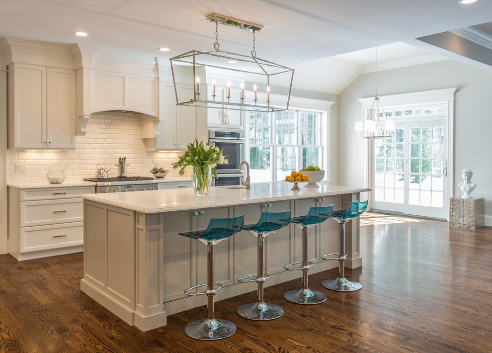 Example of a mid-sized transitional galley dark wood floor open concept kitchen design in Boston with an undermount sink, recessed-panel cabinets, white cabinets, white backsplash, subway tile backsplash, stainless steel appliances and an island
