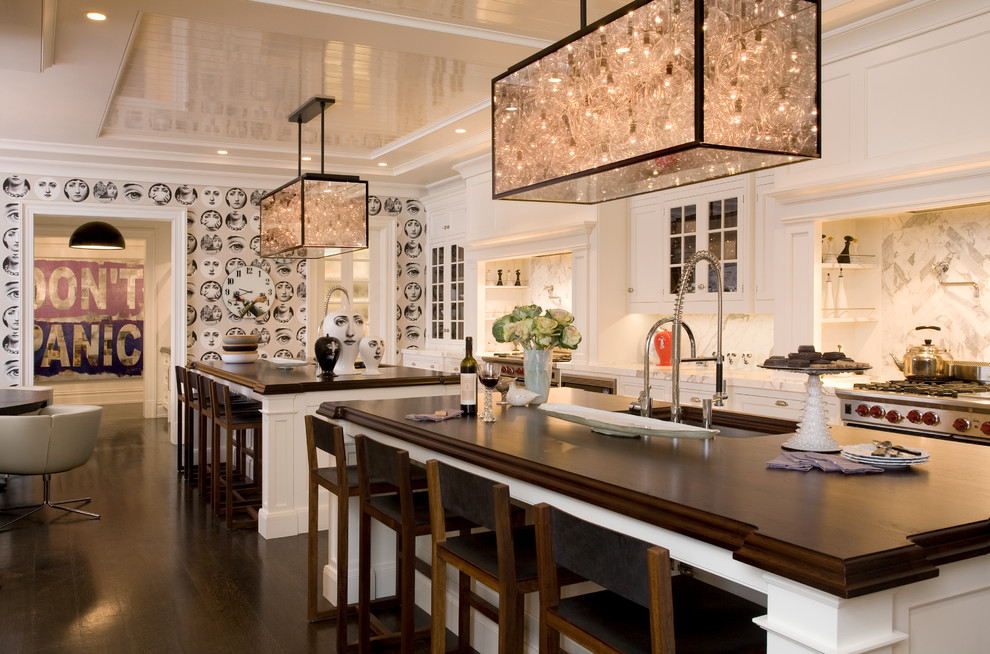 Example of a trendy eat-in kitchen design in New York with glass-front cabinets, white cabinets, wood countertops and white backsplash