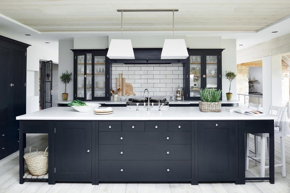 Transitional kitchen photo in London with glass-front cabinets, white backsplash, subway tile backsplash, an island and black cabinets