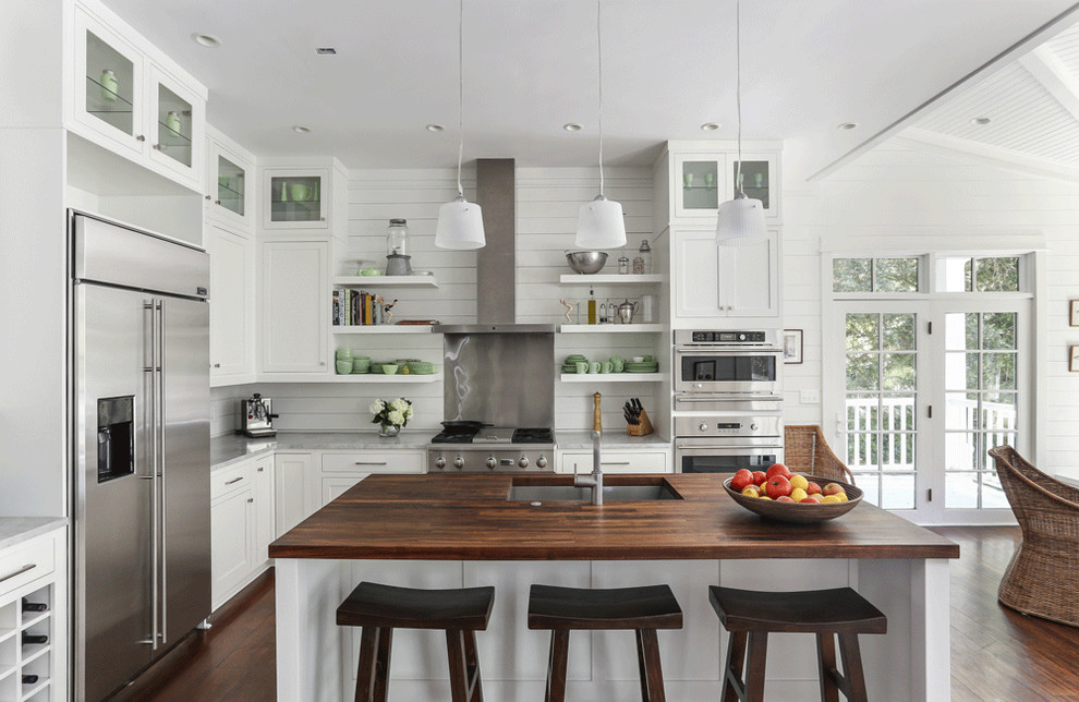 Example of a beach style l-shaped eat-in kitchen design in Charleston with a single-bowl sink, shaker cabinets, white cabinets, wood countertops and stainless steel appliances