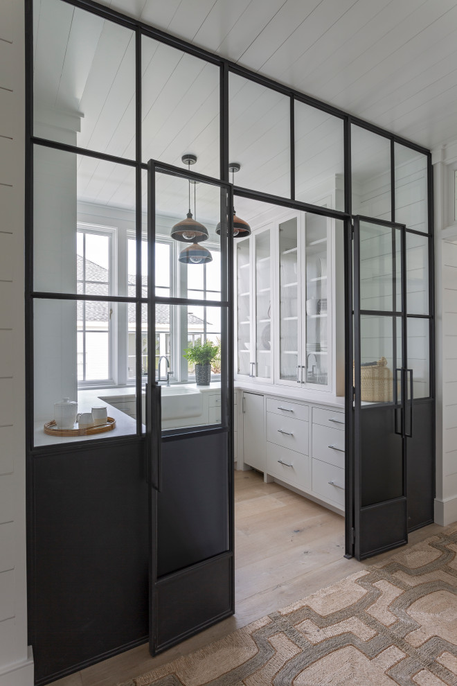 Kitchen pantry - mid-sized coastal u-shaped light wood floor and beige floor kitchen pantry idea in Charleston with a farmhouse sink, flat-panel cabinets, white cabinets, no island and white countertops