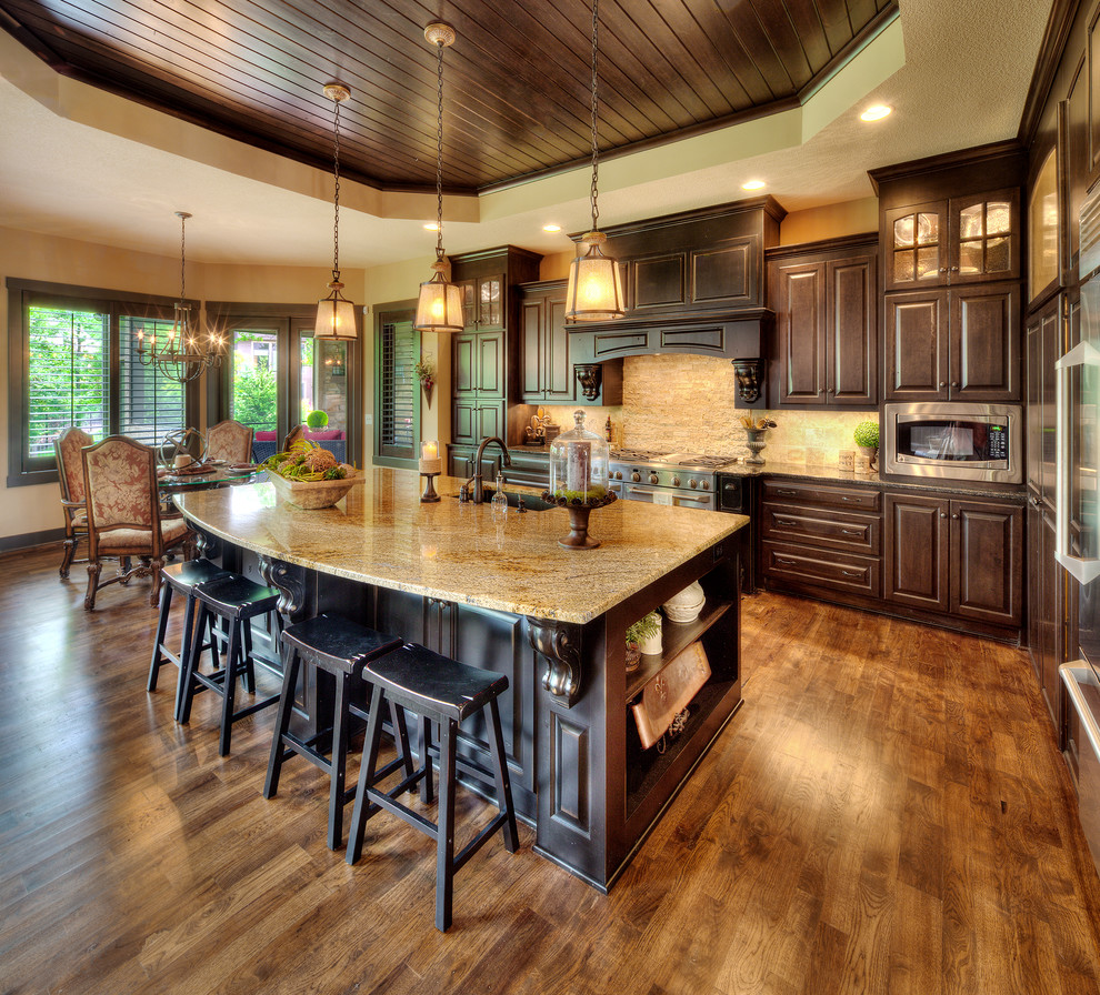 Large tuscan l-shaped kitchen photo in Kansas City with an undermount sink, raised-panel cabinets, dark wood cabinets, granite countertops, beige backsplash, stainless steel appliances and an island