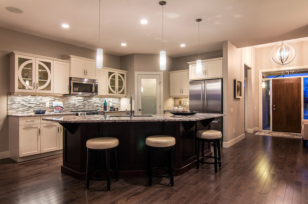 Large trendy dark wood floor open concept kitchen photo in Vancouver with a double-bowl sink, shaker cabinets, white cabinets, granite countertops, beige backsplash, matchstick tile backsplash, stainless steel appliances and an island