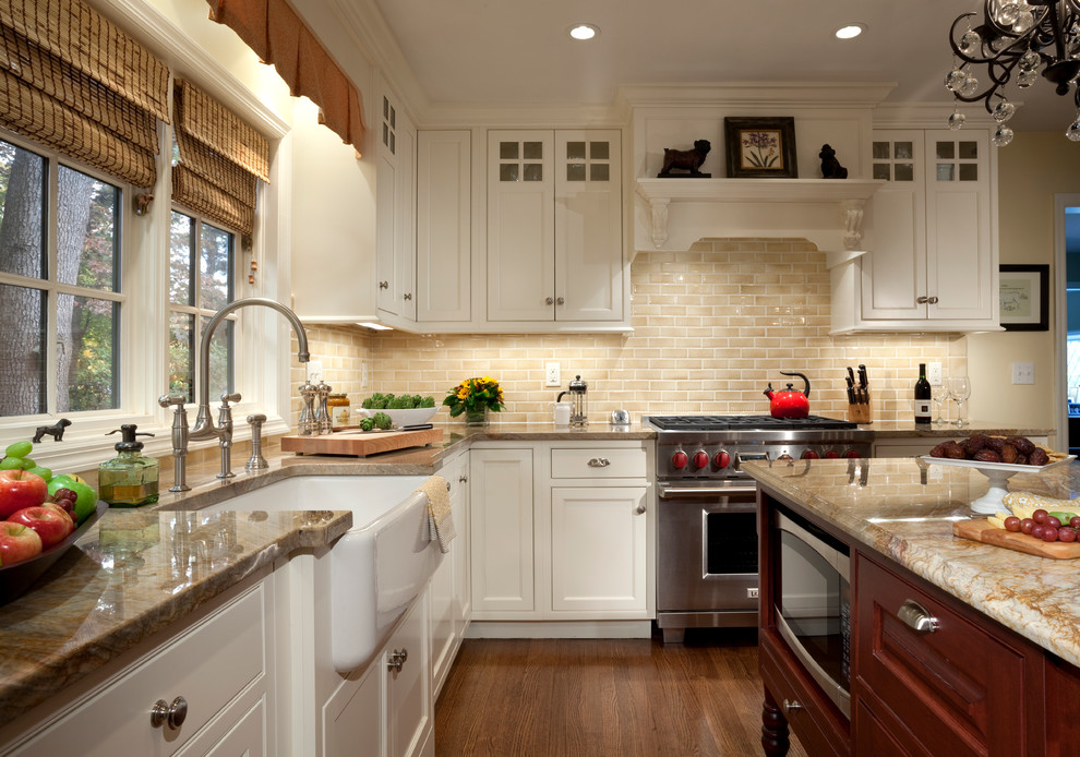 Example of a classic kitchen design in New York with stainless steel appliances, subway tile backsplash, a farmhouse sink and quartzite countertops