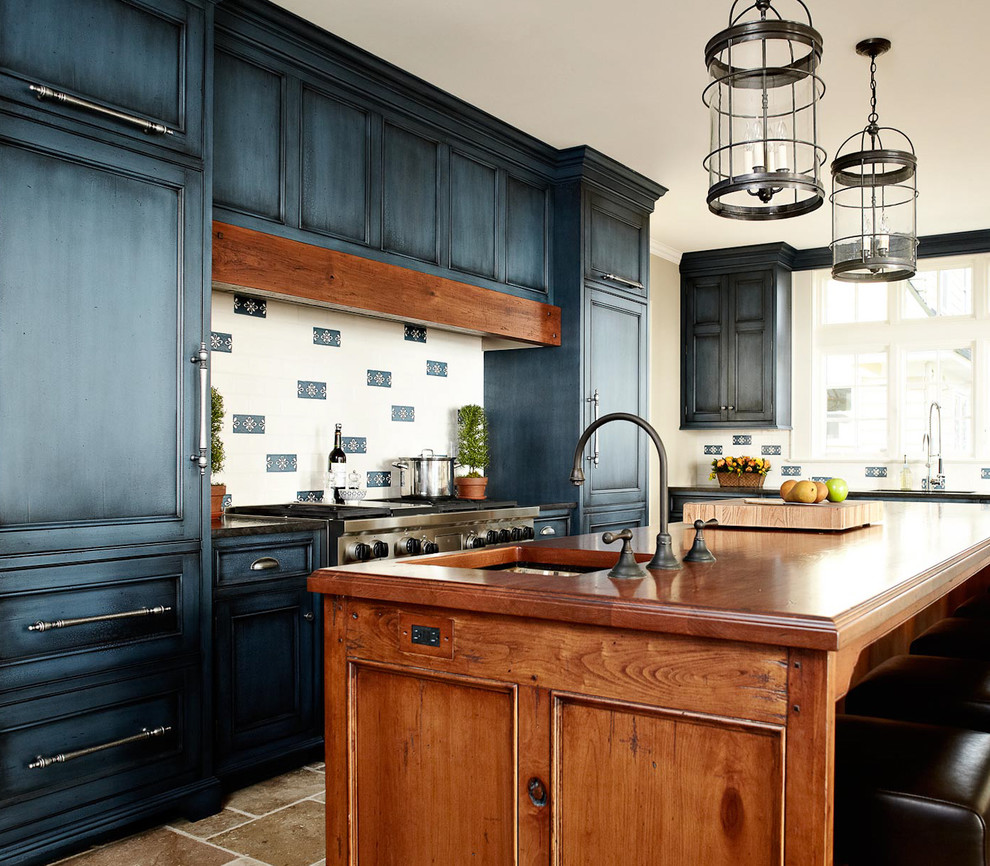 Elegant kitchen photo in New York with wood countertops, recessed-panel cabinets, blue cabinets and paneled appliances