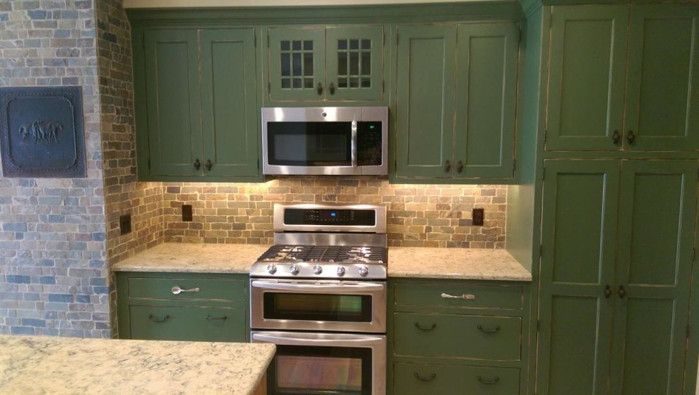 Kitchen - mid-sized cottage u-shaped light wood floor kitchen idea in Other with shaker cabinets, green cabinets, granite countertops, multicolored backsplash, stone tile backsplash, an island, a farmhouse sink and stainless steel appliances