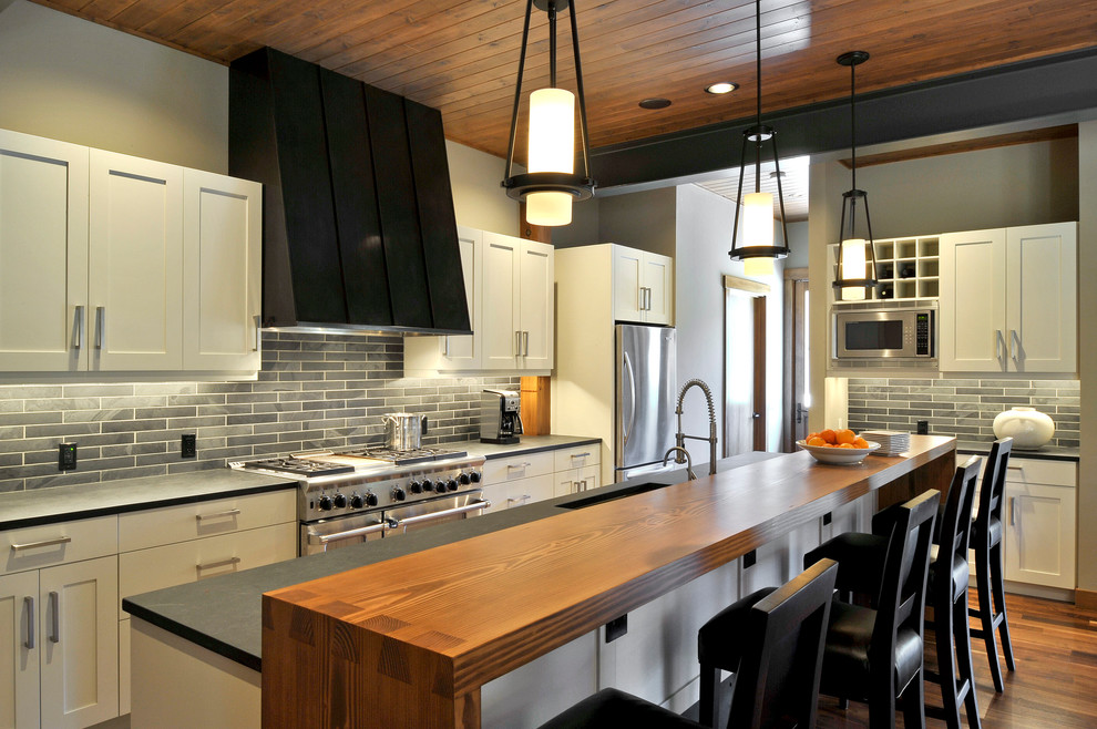 Example of a transitional galley dark wood floor kitchen design in Seattle with stainless steel appliances, wood countertops, black backsplash, an island and a single-bowl sink