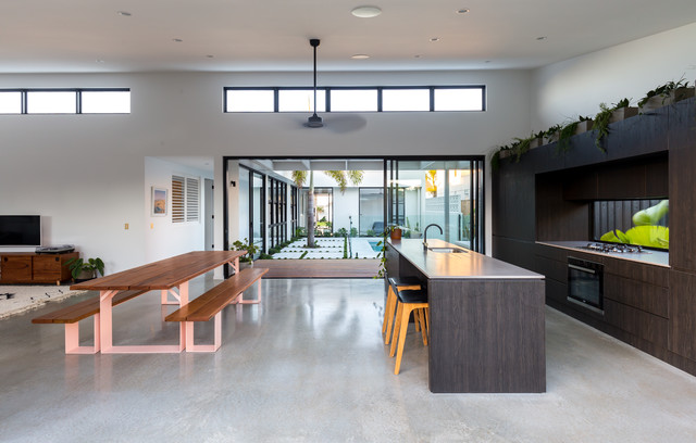 Design ideas for a contemporary galley open plan kitchen in Gold Coast - Tweed with an undermount sink, flat-panel cabinets, dark wood cabinets, window splashback, concrete floors, an island, grey floor and white benchtop.