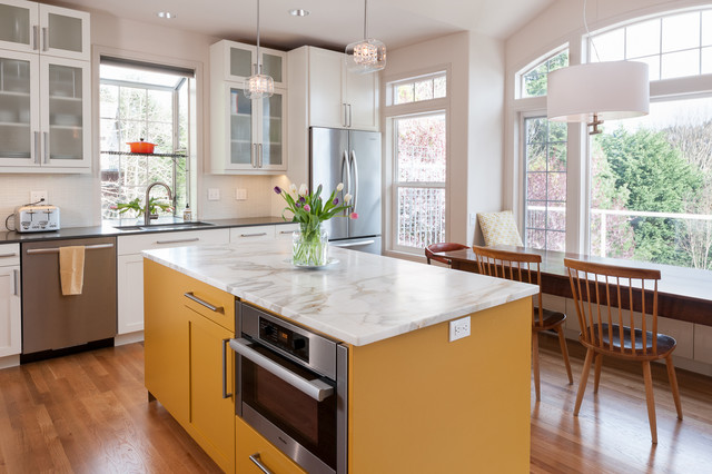 Mid-sized trendy l-shaped light wood floor open concept kitchen photo in Seattle with a double-bowl sink, shaker cabinets, yellow cabinets, marble countertops, white backsplash, glass tile backsplash, stainless steel appliances and an island