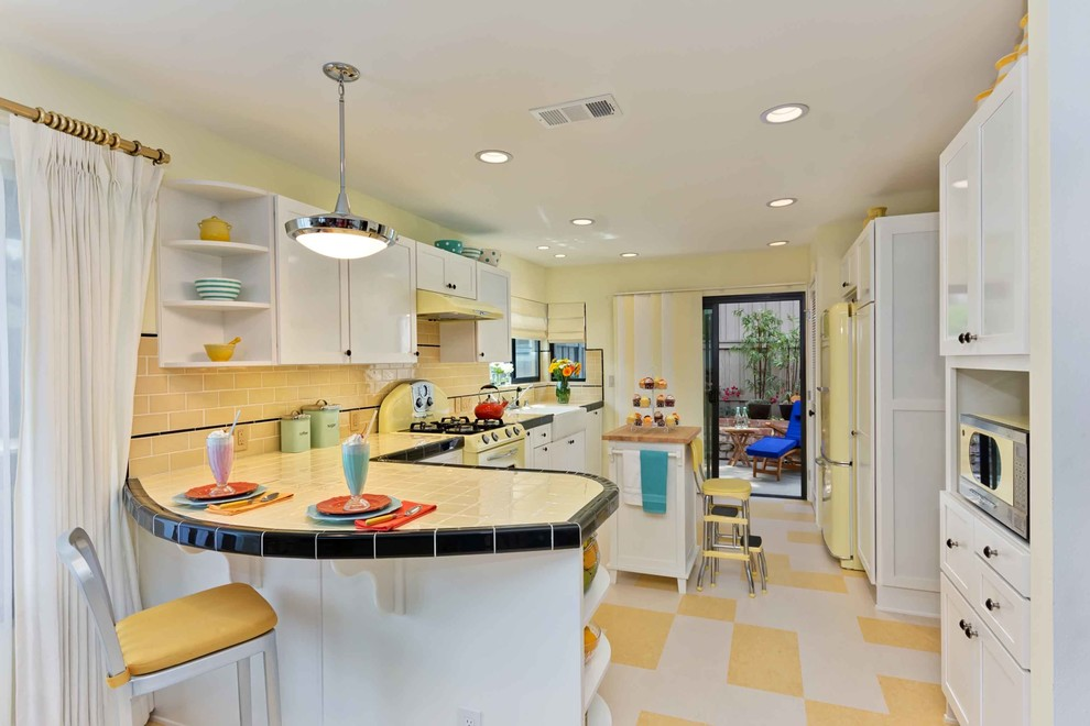Elegant u-shaped multicolored floor enclosed kitchen photo in San Diego with a farmhouse sink, shaker cabinets, white cabinets, tile countertops, yellow backsplash, subway tile backsplash, colored appliances and yellow countertops