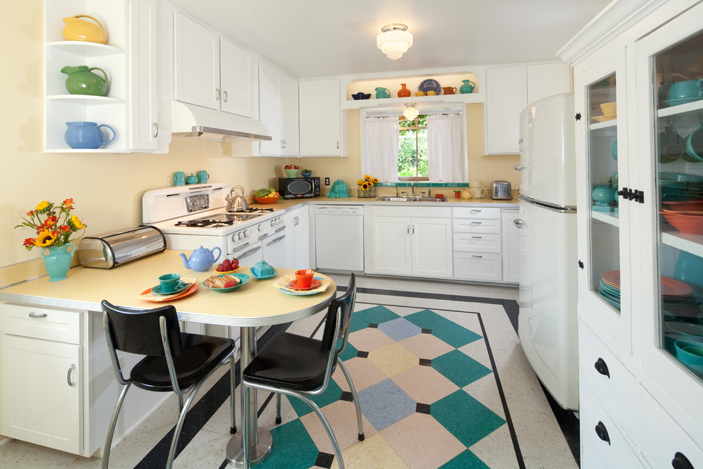 Inspiration for a mid-sized 1960s u-shaped linoleum floor and multicolored floor kitchen remodel in Santa Barbara with a double-bowl sink, shaker cabinets, white cabinets, laminate countertops, white appliances, an island and white countertops