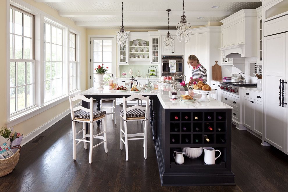 Mid-sized elegant l-shaped dark wood floor open concept kitchen photo in Minneapolis with white cabinets, an undermount sink, shaker cabinets, marble countertops, white backsplash, ceramic backsplash, stainless steel appliances and an island