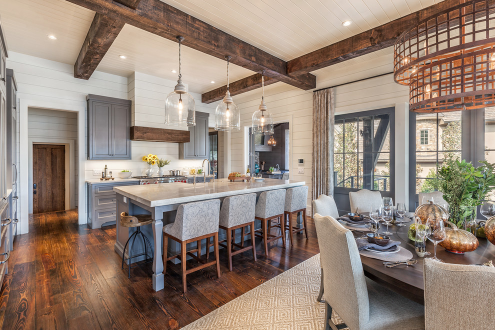 Example of a large farmhouse galley dark wood floor open concept kitchen design in Other with a farmhouse sink, shaker cabinets, gray cabinets, marble countertops, white backsplash, wood backsplash, stainless steel appliances and an island