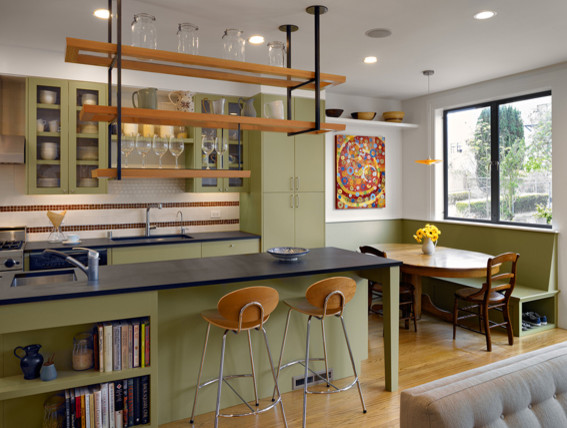 Open concept kitchen - mid-sized eclectic u-shaped light wood floor open concept kitchen idea in San Francisco with an undermount sink, glass-front cabinets, green cabinets, white backsplash, ceramic backsplash, an island, stainless steel appliances and granite countertops