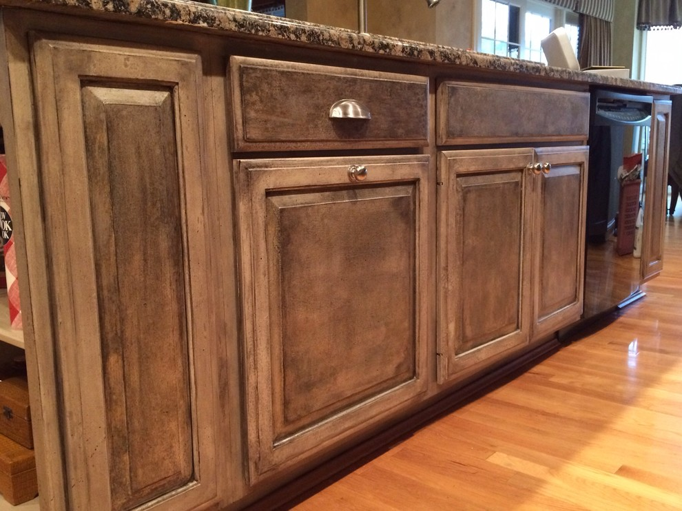 Eat-in kitchen - large craftsman l-shaped light wood floor and brown floor eat-in kitchen idea in Cincinnati with raised-panel cabinets, dark wood cabinets, an undermount sink, granite countertops, stainless steel appliances and an island
