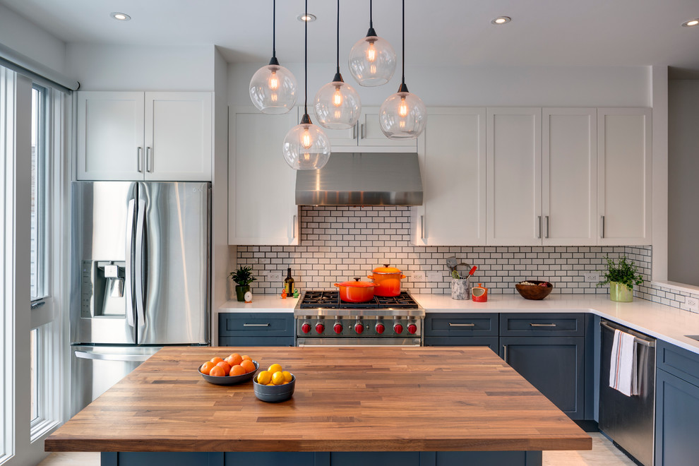 Transitional l-shaped light wood floor kitchen photo in New York with shaker cabinets, gray cabinets, quartz countertops, white backsplash, stainless steel appliances, an island and subway tile backsplash
