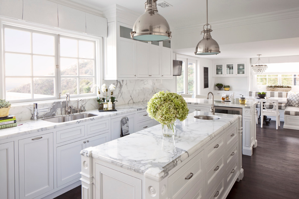 Inspiration for a mid-sized timeless l-shaped dark wood floor and brown floor eat-in kitchen remodel in Los Angeles with an undermount sink, recessed-panel cabinets, white cabinets, white backsplash, marble countertops, stone slab backsplash, stainless steel appliances and an island