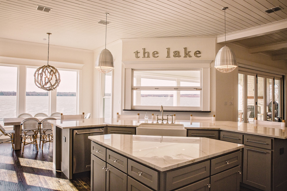 Open concept kitchen - large coastal l-shaped dark wood floor and brown floor open concept kitchen idea in Dallas with a farmhouse sink, shaker cabinets, white cabinets, marble countertops, white backsplash, ceramic backsplash, stainless steel appliances and two islands