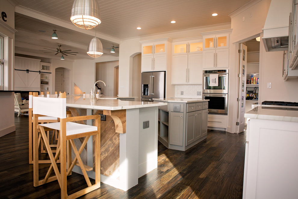 Example of a large beach style l-shaped dark wood floor and brown floor open concept kitchen design in Dallas with a farmhouse sink, shaker cabinets, white cabinets, marble countertops, white backsplash, ceramic backsplash, stainless steel appliances and two islands