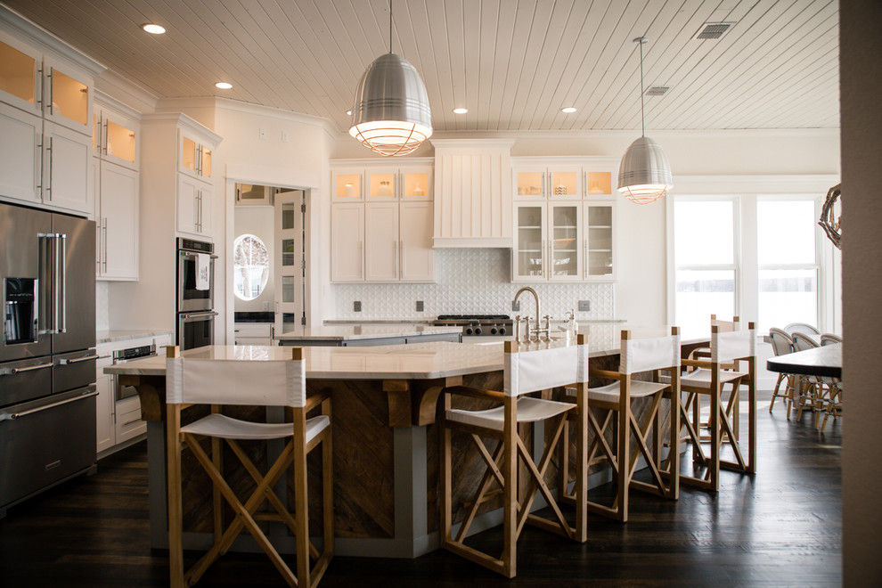Large beach style l-shaped dark wood floor and brown floor open concept kitchen photo in Dallas with shaker cabinets, white cabinets, two islands, marble countertops, white backsplash, a farmhouse sink, ceramic backsplash and stainless steel appliances