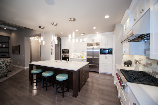 Large trendy l-shaped dark wood floor and brown floor open concept kitchen photo in Salt Lake City with an undermount sink, shaker cabinets, white cabinets, soapstone countertops, multicolored backsplash, porcelain backsplash, stainless steel appliances and an island