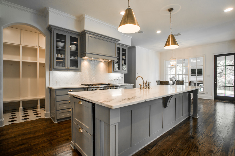Inspiration for a mid-sized transitional galley dark wood floor and brown floor eat-in kitchen remodel in Dallas with a farmhouse sink, shaker cabinets, gray cabinets, marble countertops, white backsplash, ceramic backsplash, stainless steel appliances and an island