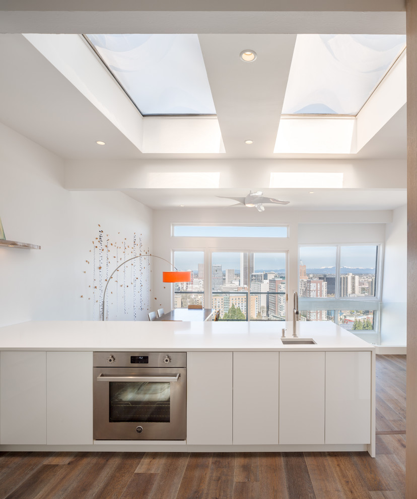Example of a minimalist eat-in kitchen design in Portland with flat-panel cabinets, white cabinets and an island