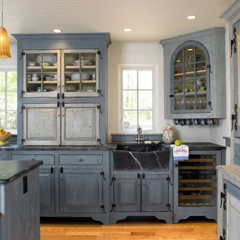 Example of a large country single-wall light wood floor and brown floor eat-in kitchen design in Philadelphia with a single-bowl sink, blue cabinets, white backsplash, stainless steel appliances, an island, soapstone countertops and raised-panel cabinets