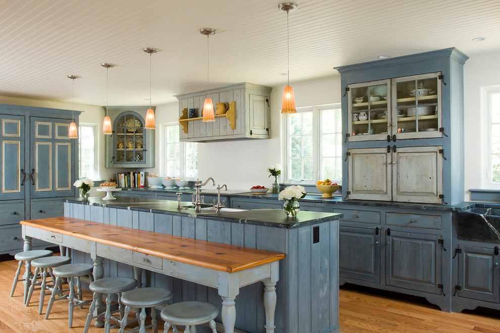 Kitchen - traditional galley medium tone wood floor and brown floor kitchen idea in Philadelphia with a farmhouse sink, raised-panel cabinets, blue cabinets, paneled appliances and an island