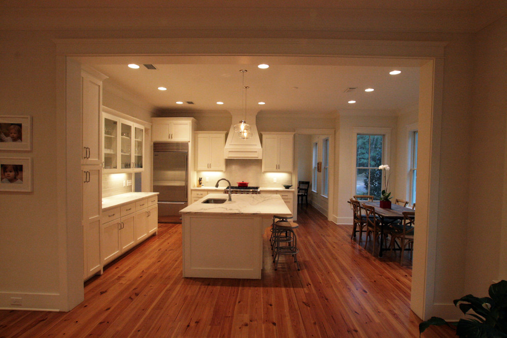 Example of a mid-sized classic l-shaped medium tone wood floor eat-in kitchen design in Other with a drop-in sink, flat-panel cabinets, white cabinets, marble countertops, white backsplash, subway tile backsplash, stainless steel appliances and an island