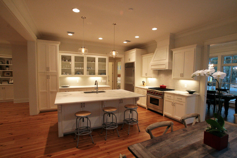 Inspiration for a mid-sized timeless l-shaped medium tone wood floor eat-in kitchen remodel in Other with a drop-in sink, flat-panel cabinets, white cabinets, marble countertops, white backsplash, subway tile backsplash, stainless steel appliances and an island