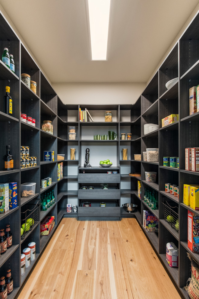 Example of a trendy u-shaped medium tone wood floor and brown floor kitchen pantry design in Portland with open cabinets, black cabinets and no island