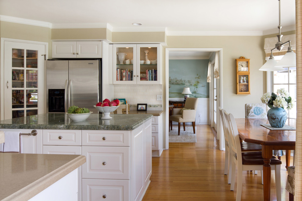 Eat-in kitchen - traditional eat-in kitchen idea in Los Angeles with raised-panel cabinets, white cabinets, white backsplash, subway tile backsplash and stainless steel appliances