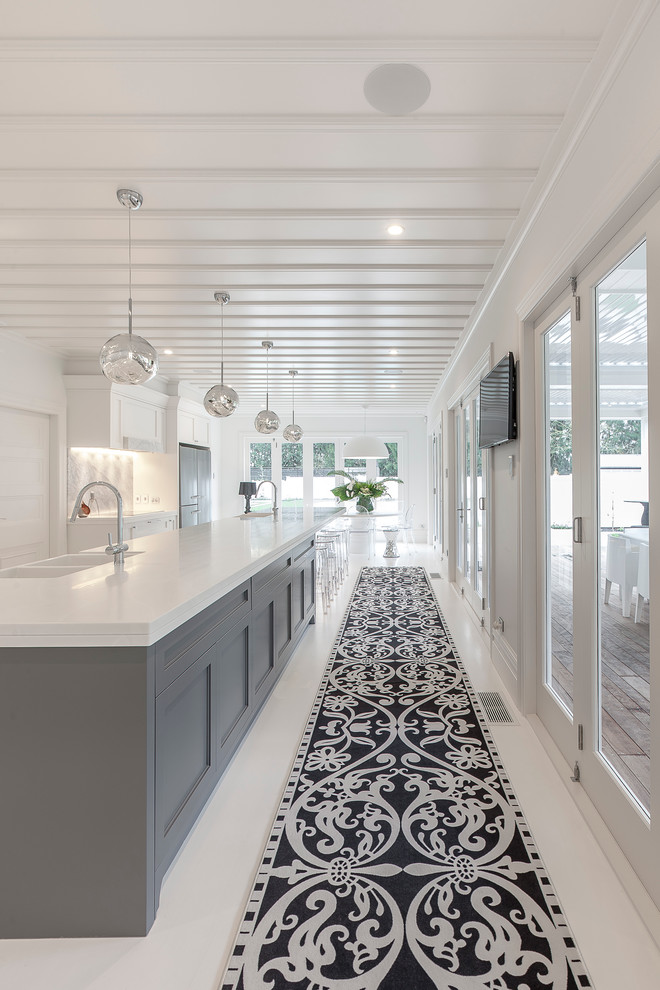 Inspiration for a huge transitional eat-in kitchen remodel in Auckland with a farmhouse sink, recessed-panel cabinets, white cabinets, solid surface countertops, multicolored backsplash, stone slab backsplash, black appliances and an island