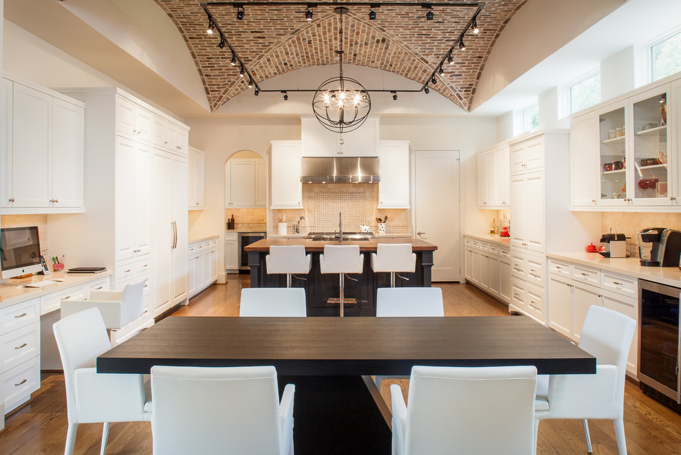 Eat-in kitchen - large transitional u-shaped medium tone wood floor and brown floor eat-in kitchen idea in Houston with a farmhouse sink, raised-panel cabinets, white cabinets, wood countertops, beige backsplash, stone tile backsplash, paneled appliances and an island
