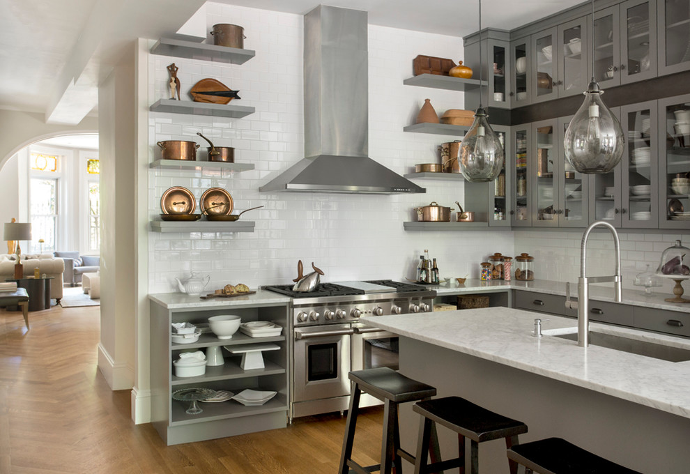 Inspiration for a large transitional l-shaped light wood floor open concept kitchen remodel in Boston with an undermount sink, glass-front cabinets, gray cabinets, marble countertops, white backsplash, porcelain backsplash, stainless steel appliances and an island
