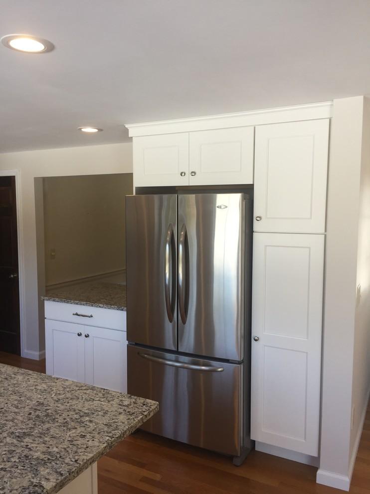 Ejemplo de cocina clásica, de tamaño medio, con fregadero bajoencimera, armarios estilo shaker, puertas de armario blancas, encimera de granito, salpicadero beige, salpicadero de azulejos de porcelana, electrodomésticos de acero inoxidable, suelo de madera clara y una isla