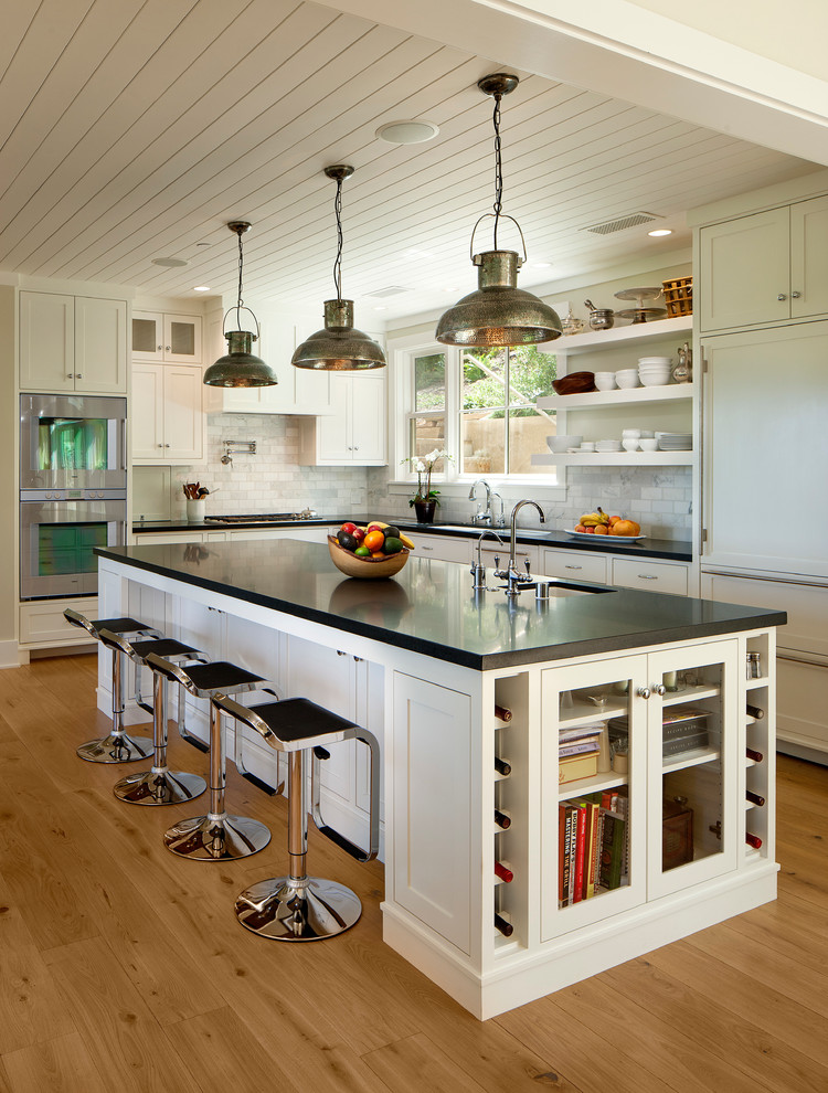 Inspiration for a large timeless l-shaped light wood floor kitchen remodel in Santa Barbara with an undermount sink, shaker cabinets, white cabinets, white backsplash, paneled appliances, an island and black countertops