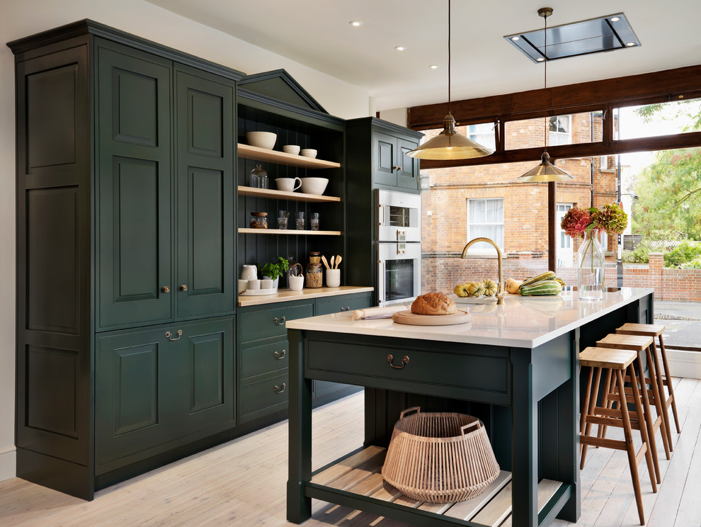 Kitchen - traditional galley light wood floor kitchen idea in Oxfordshire with recessed-panel cabinets, green cabinets, stainless steel appliances and an island