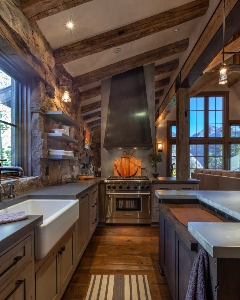 Mid-sized mountain style u-shaped dark wood floor, brown floor and exposed beam enclosed kitchen photo in Denver with a farmhouse sink, shaker cabinets, an island, gray countertops, distressed cabinets, concrete countertops, brown backsplash, stone tile backsplash and paneled appliances