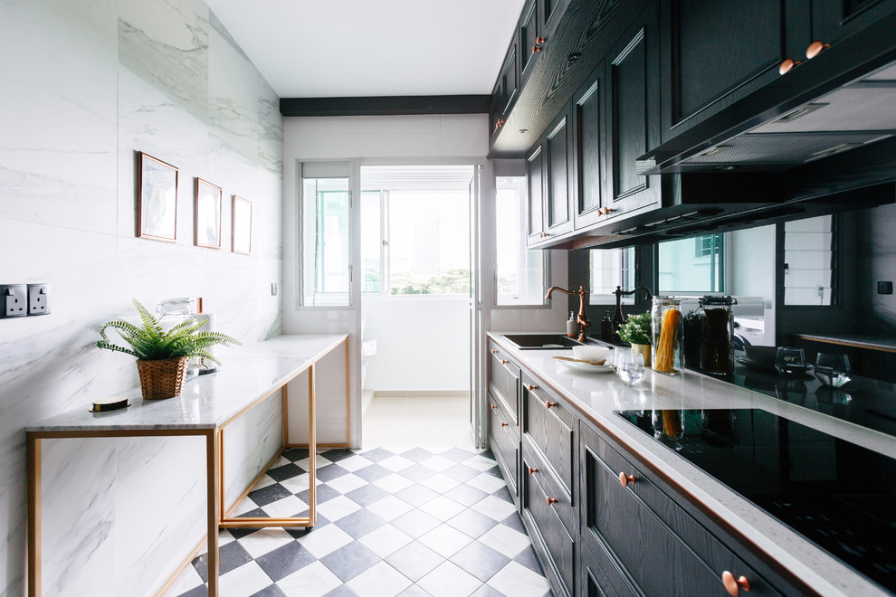 Example of a transitional single-wall black floor enclosed kitchen design in Singapore with a drop-in sink, recessed-panel cabinets, black cabinets, black backsplash, glass sheet backsplash, black appliances, a peninsula and beige countertops