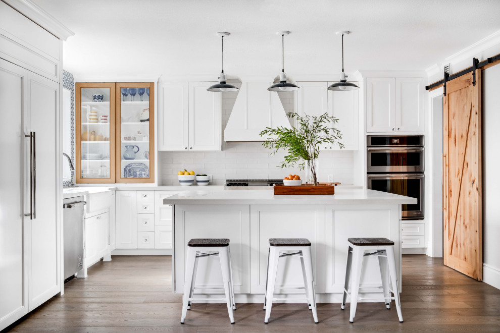 Inspiration for a transitional l-shaped dark wood floor and brown floor kitchen remodel in Orange County with a farmhouse sink, stainless steel appliances, an island, shaker cabinets, white cabinets, white backsplash and white countertops