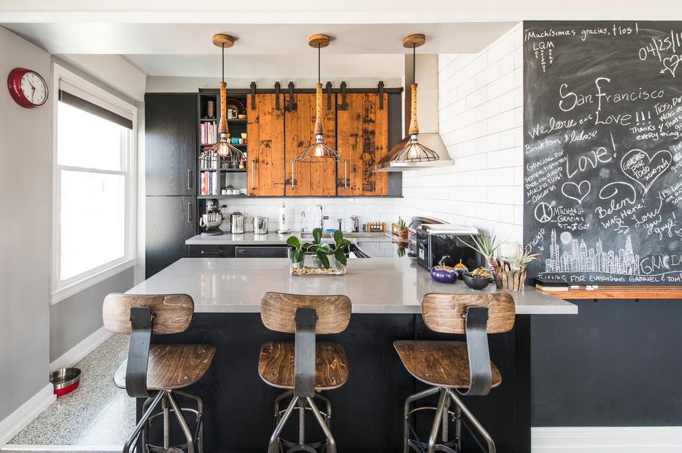 Mid-sized urban u-shaped enclosed kitchen photo in San Francisco with flat-panel cabinets, black cabinets, white backsplash, subway tile backsplash, a peninsula, an undermount sink, quartz countertops and stainless steel appliances