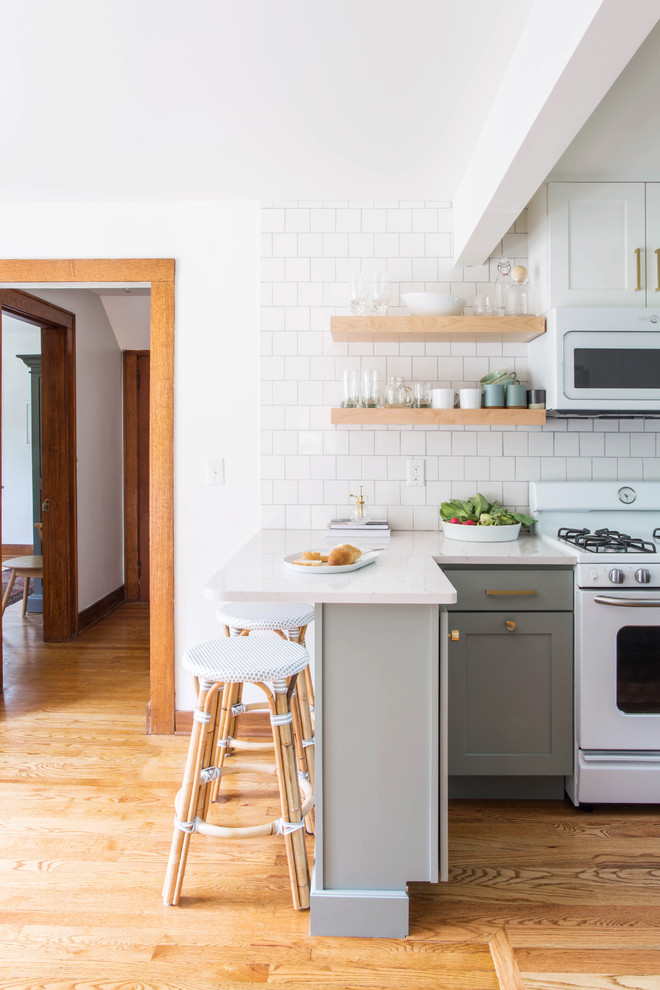 Small transitional u-shaped medium tone wood floor and brown floor eat-in kitchen photo in Other with a farmhouse sink, shaker cabinets, blue cabinets, quartz countertops, white backsplash, porcelain backsplash, white appliances and a peninsula
